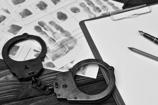 Handcuffs, fingerprints of the detained criminal, a blank sheet of paper on the background of a wooden table.