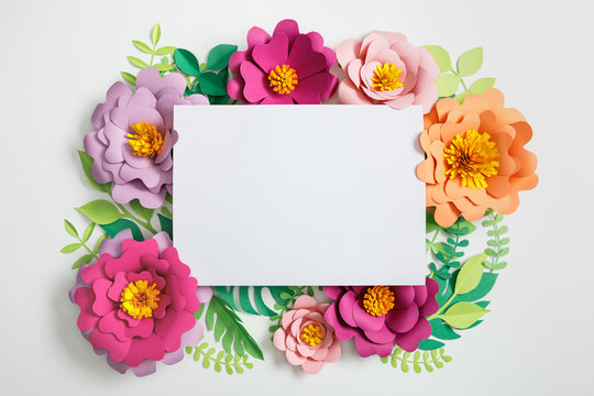 top view of white blank card on multicolored paper flowers with green leaves on grey background