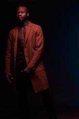 Full length portrait of dancing shirtless man in brown coat and jeans. Studio shot, dark key