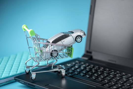 Shopping basket with car on laptop keyboard on blue background. Concept of online shopping vehicles on the Internet