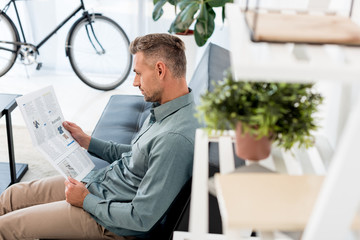 selective focus of businessman reading business newspaper in office