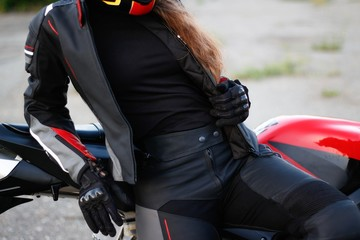 Beautiful girl motorcyclist in full gear and helmet on a red and black sportbike