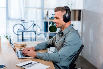 cheerful businessman listening music in headphones while using laptop in modern office