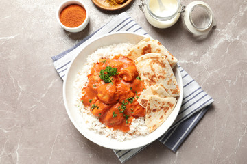 Delicious butter chicken with rice served on table, flat lay