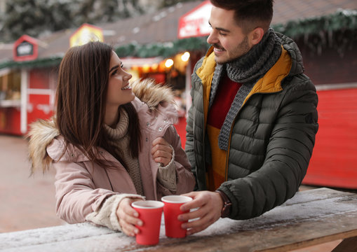Young couple with cups of mulled wine at winter fair