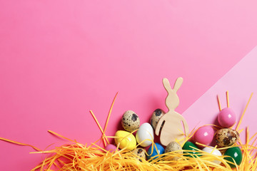 Flat lay composition of Easter bunny figure and eggs on color background, space for text