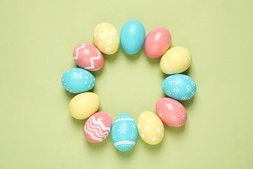 Flat lay composition of painted Easter eggs on color background, space for text