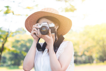 Asian woman photographer is taking photo by using vintage film camera.