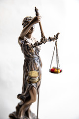 statue of justice with pills and money balance