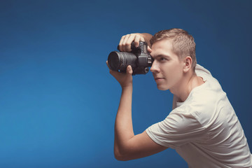 Smiling Man with camera isolated on blue background. Young man holding digital camera and making photo looking on side. Lifestyle, travel and technology concept. Happy boy in white t-shirt with dslr