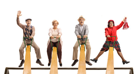 Cheerful senior people having fun on a seesaw