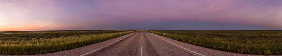 panorama of a straight road through the outback of Australia, after a beautiful sunset, Nothern territory