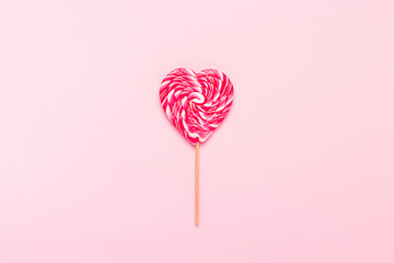 Heart shaped lollipop on a gently pink background. Flat lay, top view