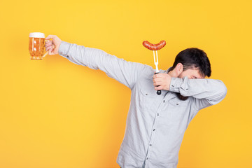 man with a glass of beer and grilled sausage on a fork in his hand, standing in dab dance pose on yellow background Wall mural