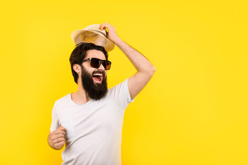 studio portrait of a cheerful bearded guy in a great mood, man in sunglasses, welcome gesture of raising the hat, concept summer vacation Wall mural