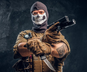 A terrorist in a military uniform and a skull balaclava holding a pistol and a knife and looks at the camera with a menacing look. Studio photo against a dark textured wall - fototapety na wymiar