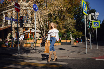 A beautiful young woman with blond curly hair walks through the sunny city