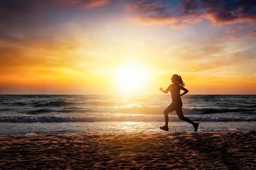 Silhouette einer sportlichen Frau die am Strand bei Sonnenuntergang trainiert