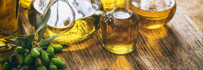 Olive oil in glass bottles on wooden table, banner, closeup view