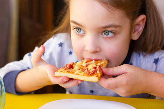 The child eats delicious pizza.
