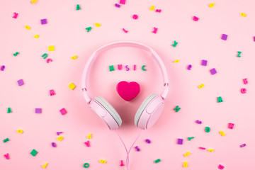 Pink headphones and heart with word MUSIC and multicolored letter symbols on pink background. Minimal Music concept. Top view. Flat lay