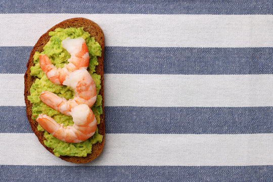 shrimp and avocado on bread with light background healthy breakfast