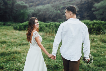 Amazing young couple exploring and holding by hands while girl is leading her boyfriend and looking at camera.