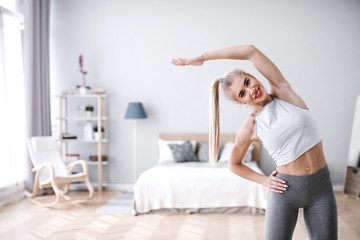 Beautiful sporty woman doing exercise at home.