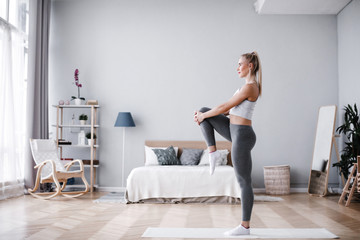 Full length portrait of attractive young woman working out at home, doing pilates exercise on mat. Wall mural