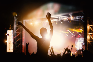 Photo of a crowd, people enjoying rock concert, raised up hands and clapping of pleasure, active night life concept