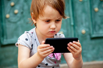 Social Media addiction. Little child girl holding smart phone. Psychological problems, media mania concept.