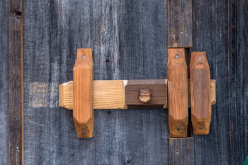 A wooden Latch lock on the door, close up.