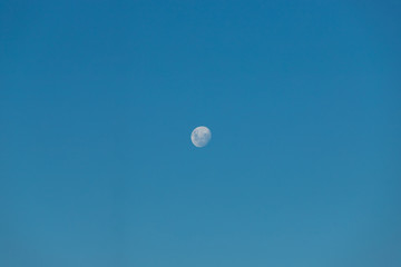 Gibbous moon phase on a clear blue sky.