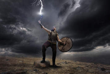 Medieval warrior berserk Viking with axe catch the lightning. Concept historical dramatic photo