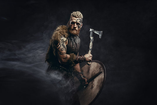 Medieval warrior berserk Viking with tattoo and in skin with axes attacks enemy. Concept historical photo