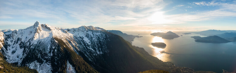 Aerial panoramic view of Howe Sound Mountains during a vibrant winter sunset. Taken near Lions Bay, North of Vancouver, BC, Canada.