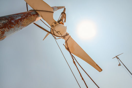 Looking up small broken wind turbine, strong midday sun shining in back