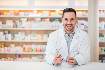 Photo sur Aluminium Pharmacie Portrait of a cheerful handsome pharmacist leaning on counter at drugstore.