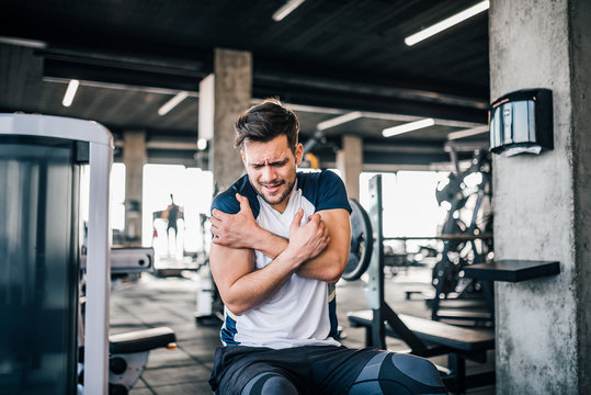 Handsome young sportsman feeling pain in shoulder while working out in the gym.