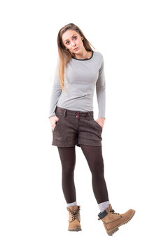 Cool young blonde woman cutie whistling with hands in pockets. Full body isolated on white background.