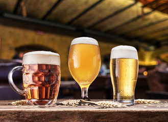 Wall Mural - Glasses of beer on the wooden table. Blurred pub interior at the background. Assortment of beer.