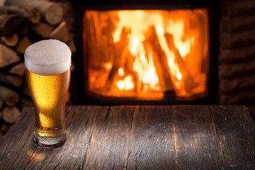 Wall Mural - Chilled glass of light beer on the wooden table. Fireplace at the background.