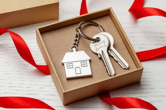 Keychain house and keys with red ribbon and gift box on white wooden background.