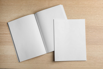 Open and closed blank brochures on wooden background, top view. Mock up for design