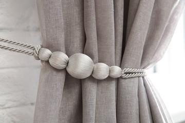 Beautiful draped window curtain with tieback in room, closeup