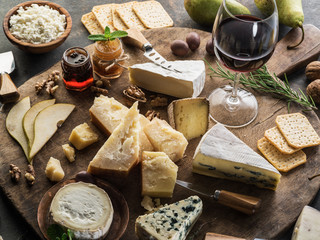 Wall Mural - Cheese platter with different cheeses, fruits, nuts and wine on stone background. Top view. Tasty cheese starter.