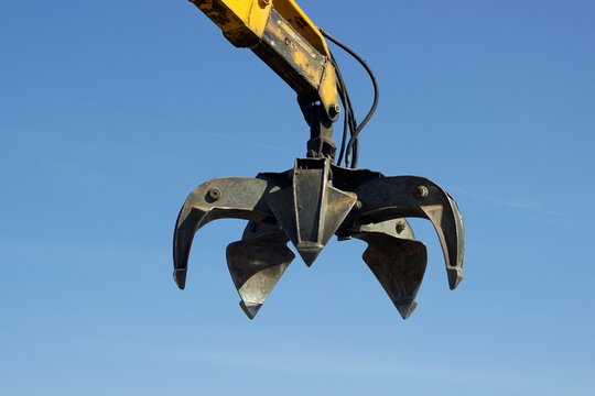 Closeup view of open claw of crane in use at recycle junkyard blue sky at background