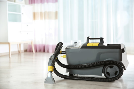 Wet and dry vacuum cleaner on floor indoors. Space for text