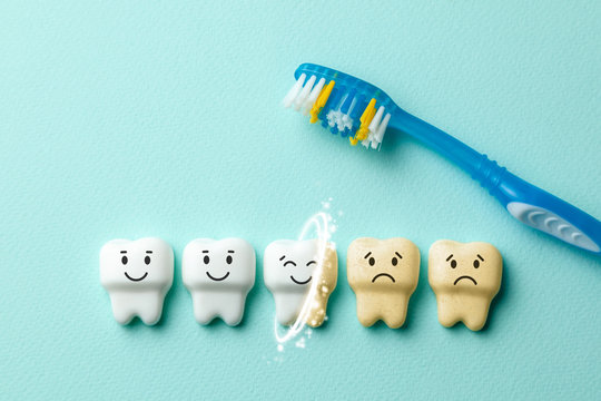 Teeth whitening. Healthy white teeth are smiling and yellow from cigarettes and sad coffee on green mint background with toothbrush