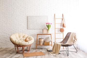 Stylish living room interior with cozy armchairs near brick wall